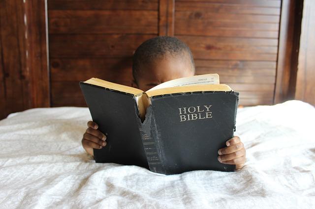 bimbo africano che legge una Bibbia